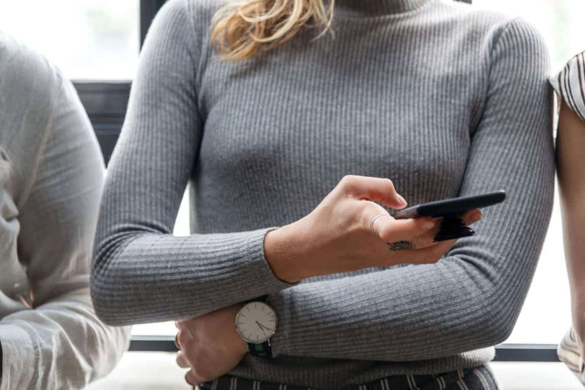 A woman checks her mobile phone.