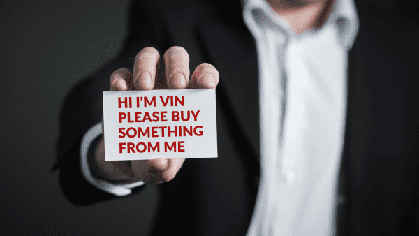 A man in suit holding out a name card.