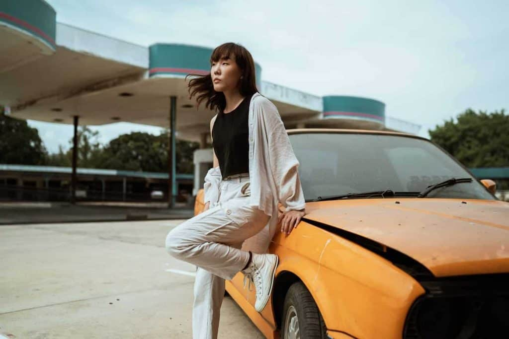 asian woman leaning on car