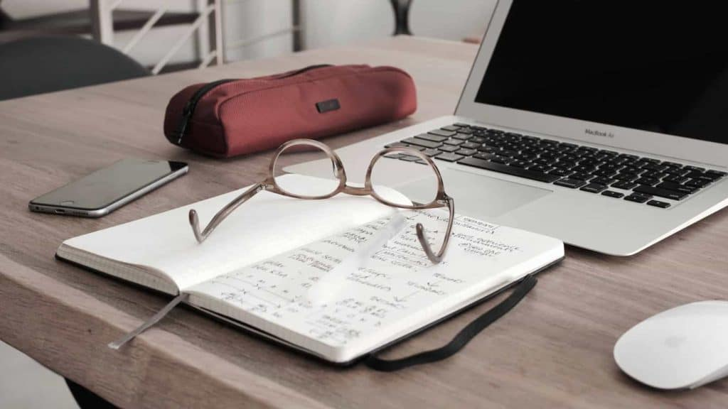 laptop on table with notebook and glasses