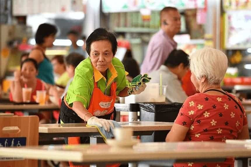 a cleaning aunty cleaning a table at the hawker centre